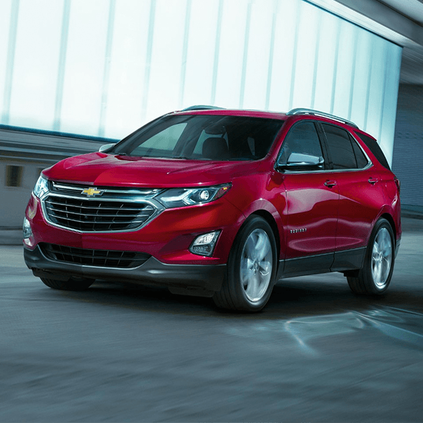 red Chevrolet Equinox Suv with the headlights on inside a parking lot
