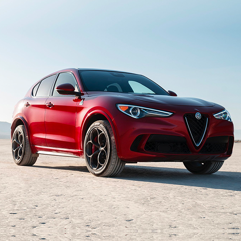 frontal profile of red alfa romeo stelvio suv parked on a desert scenery