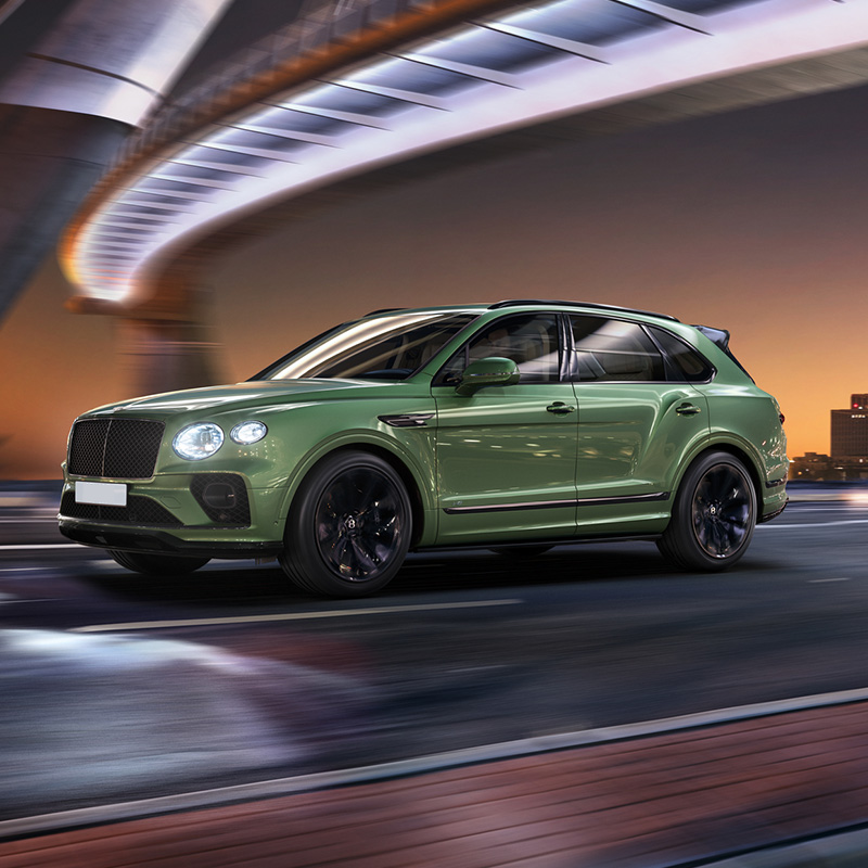 green color Bentley Bentayga suv with headlights on driving along at night under a bridge