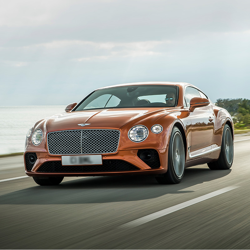 orange Bentley continental GT sedan driving along the road in the middle fo the day