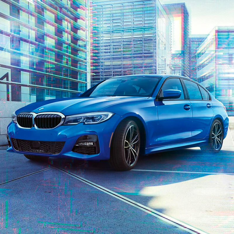 frontal view of blue BMw 3 series sedan on parking lot with building in the background