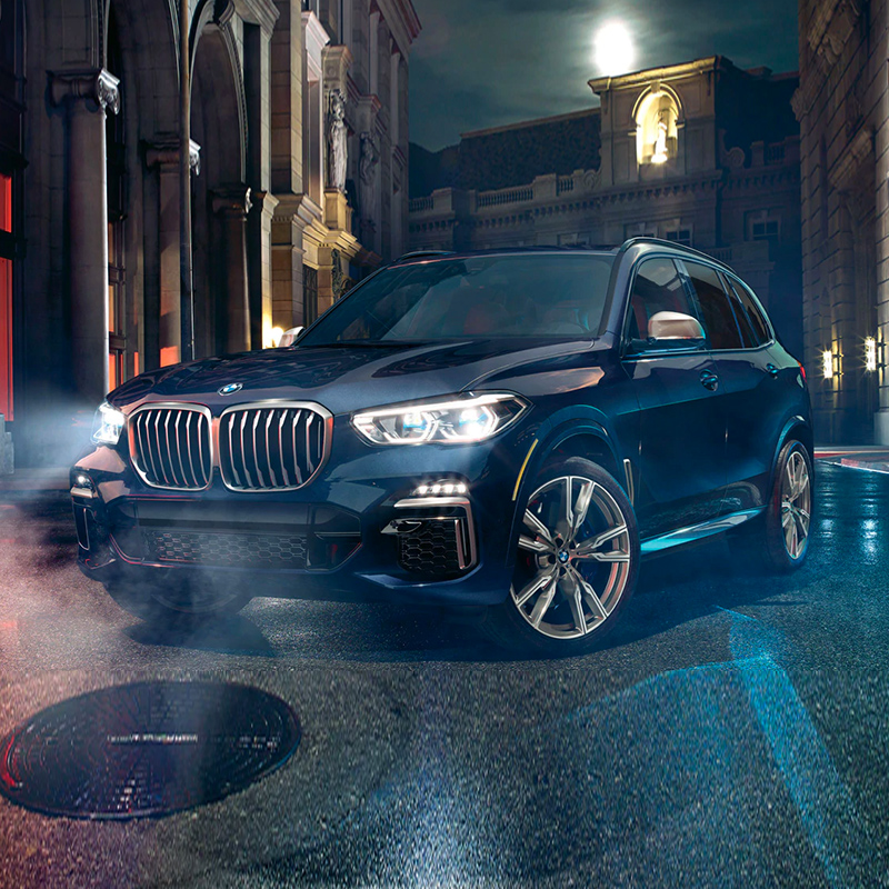 black BMW X5 suv with headlines on, parked on a street at night