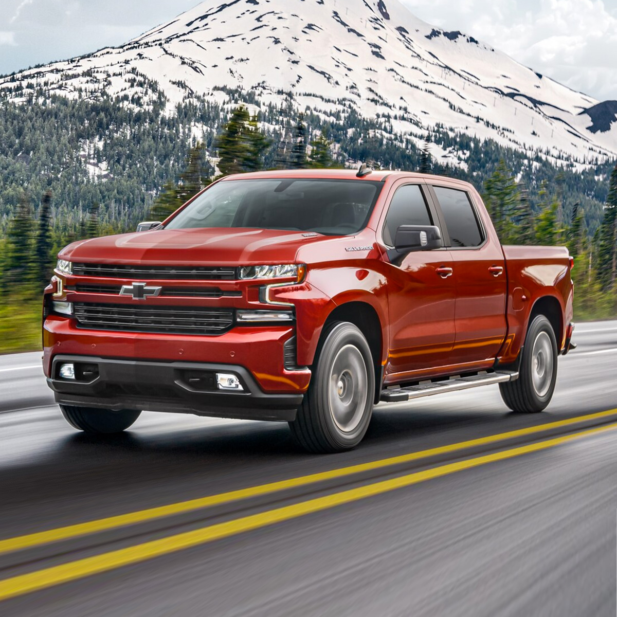 frontal profile of red chevrolet silverado pick up truck on the road with snow mountains in the background