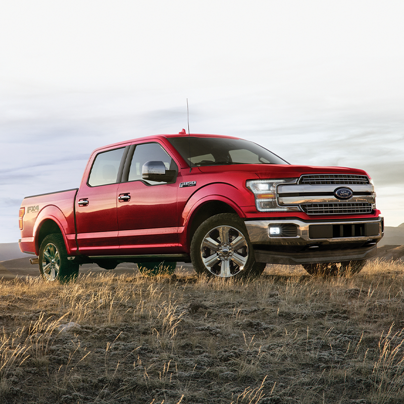 side view of red Ford F-150 on a dirt terrain with mountains in the background