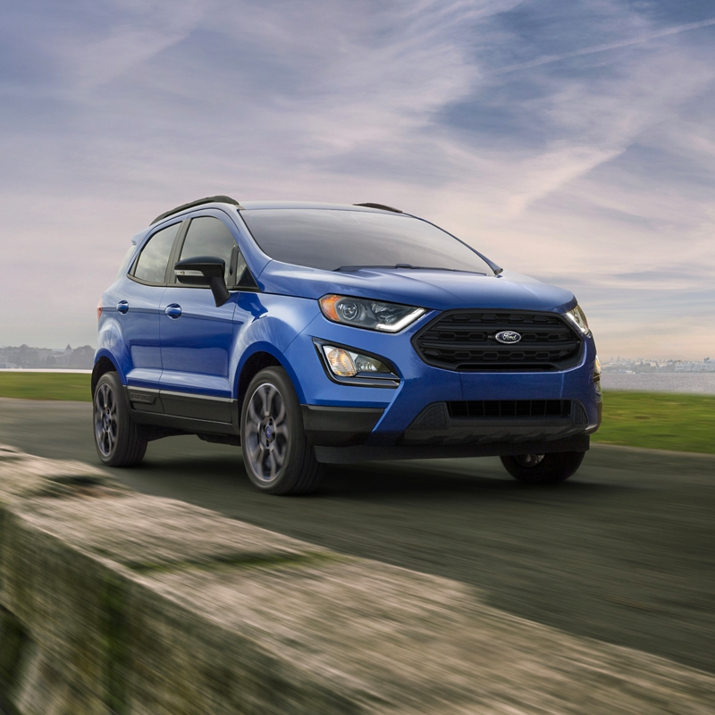 side profile of ford ecosport crossover in blue color driving on pavement road with a cloudy sky