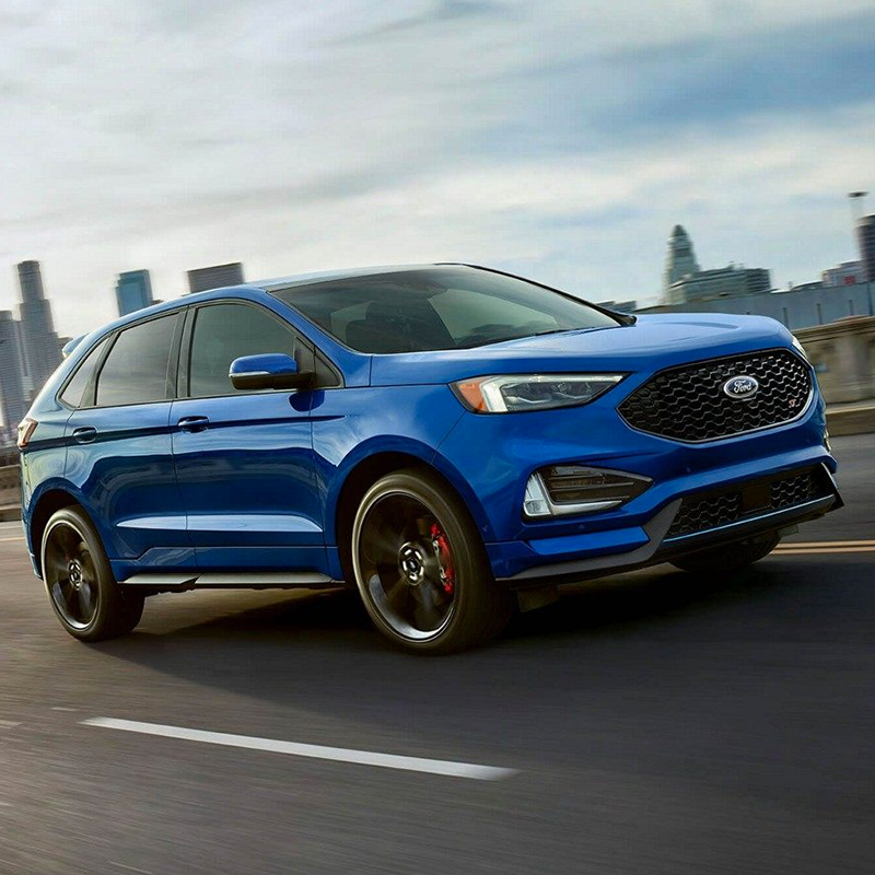 side profile of ford edge suv in blue color driving at high speed on a pavement road with buildings on the horizon