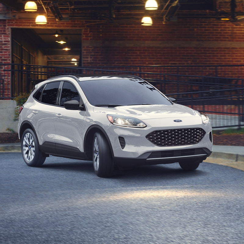 side profile of ford escape suv in white color parked in front of a red brick building