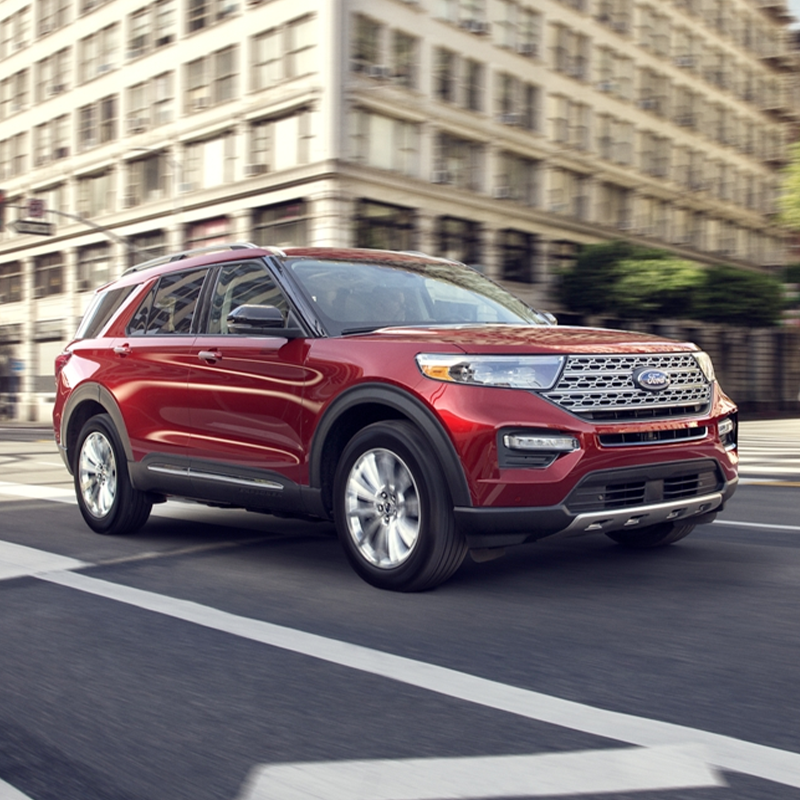 side profile of ford explorer suv in red color driving through streets surrounded by buildings