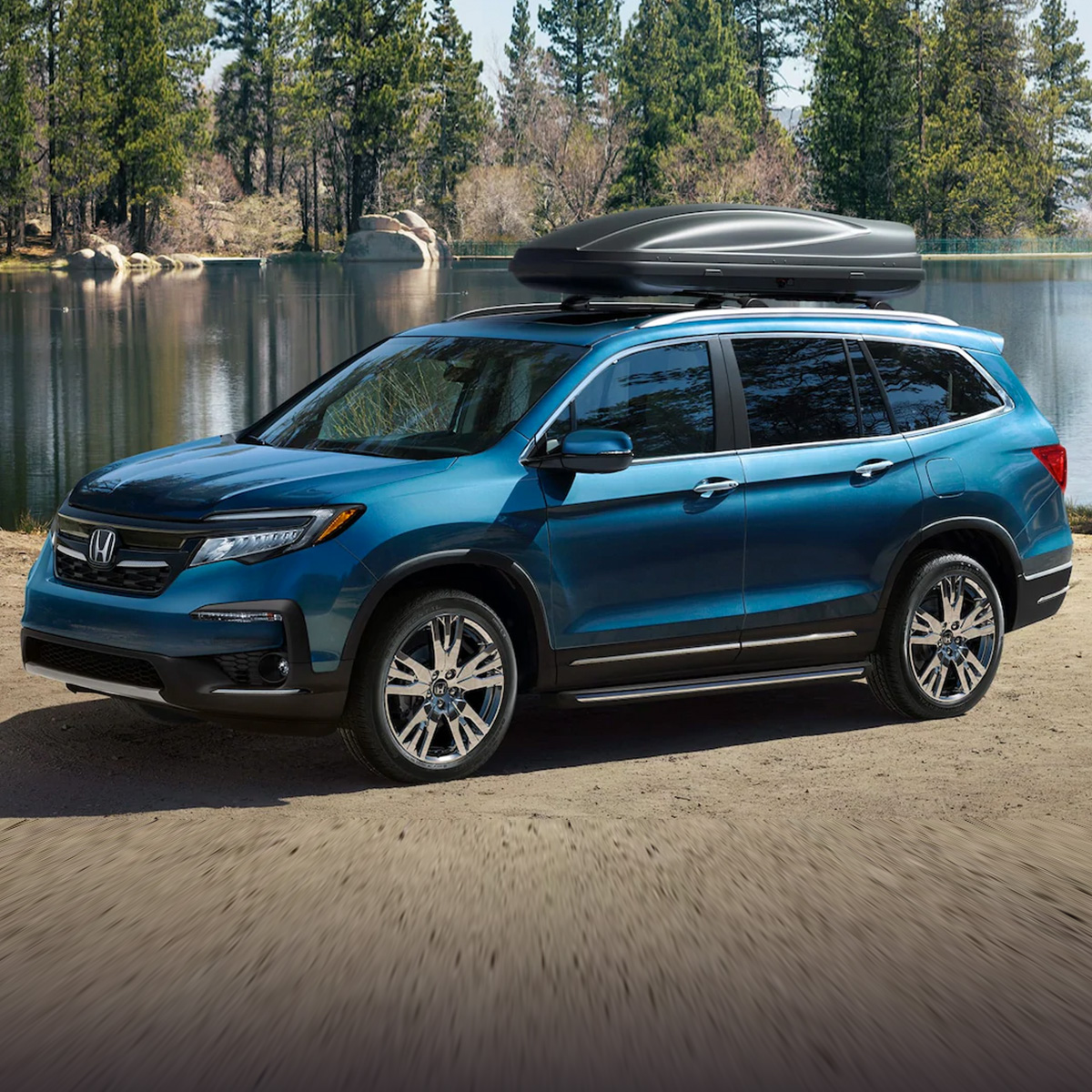 side profile view of blue honda pilot suv parked in front of lake