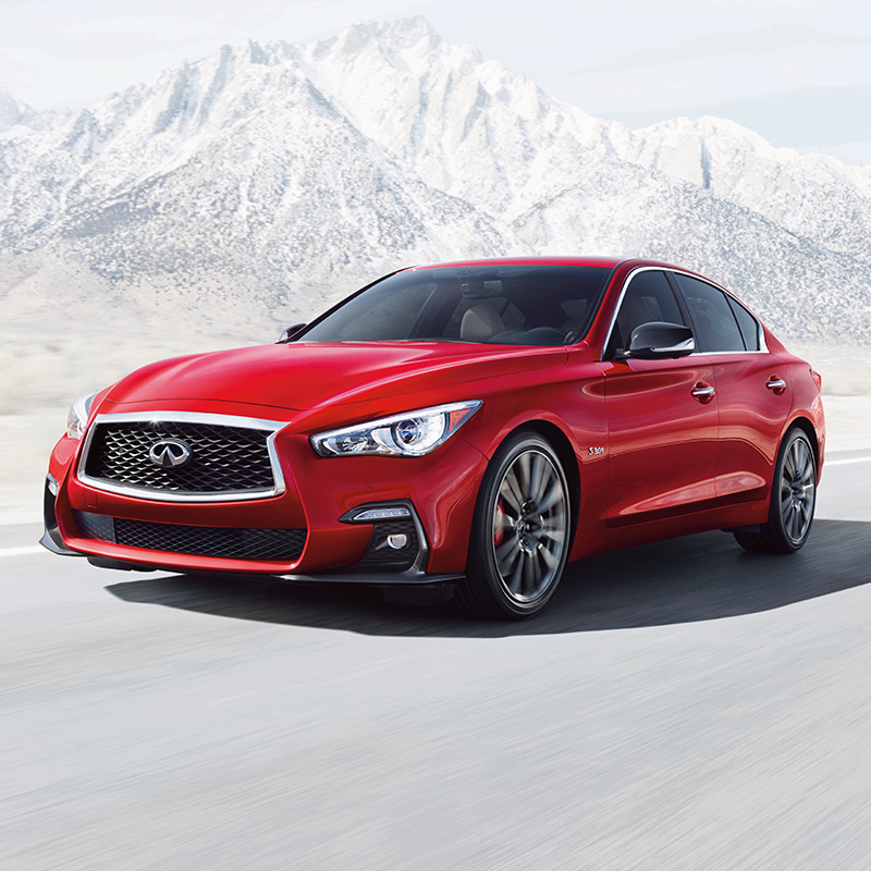 red INFINITI Q50 going at high speed on a road with snow mountains in the background