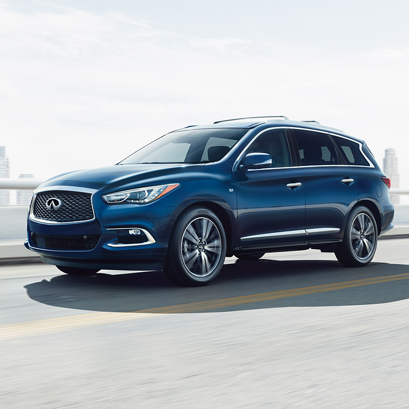 side profile of INFINITI QX60 suv in blue color driving on a bridge with buildings in the horizon