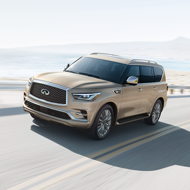 frontal profile of INFINITI QX80 suv in gold color driving on a road near a beach