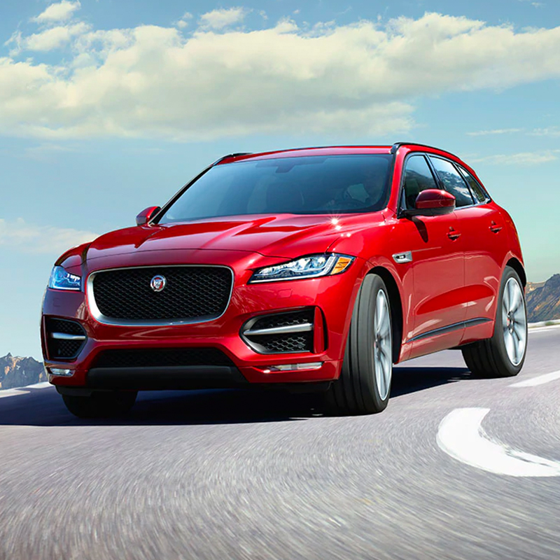 red jaguar F-pace taking a curve on a mountain