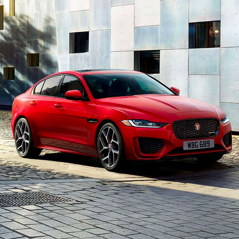 frontal profile of Jaguar Xe sedan parked in front of an architectural building