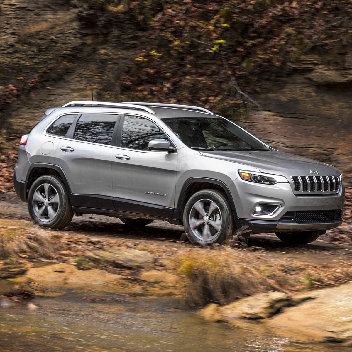 side view of silver jeep cherokee vehicle cruising on mountain terrain