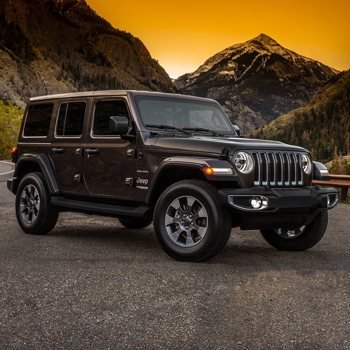 side view of jeep wrangler parked on asphalt and mountains in the background