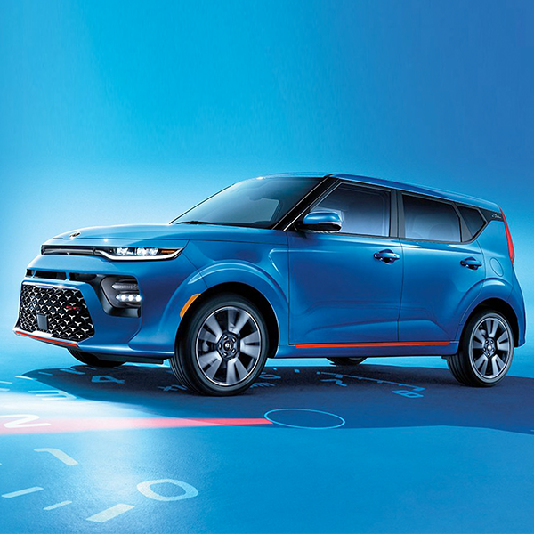 sideview of blue kia Soul with a blue studio background