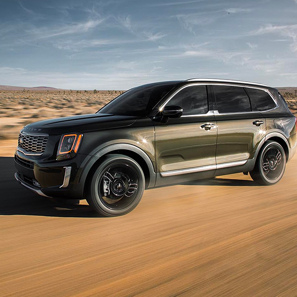dark green Kia telluride suv driving a long the desert