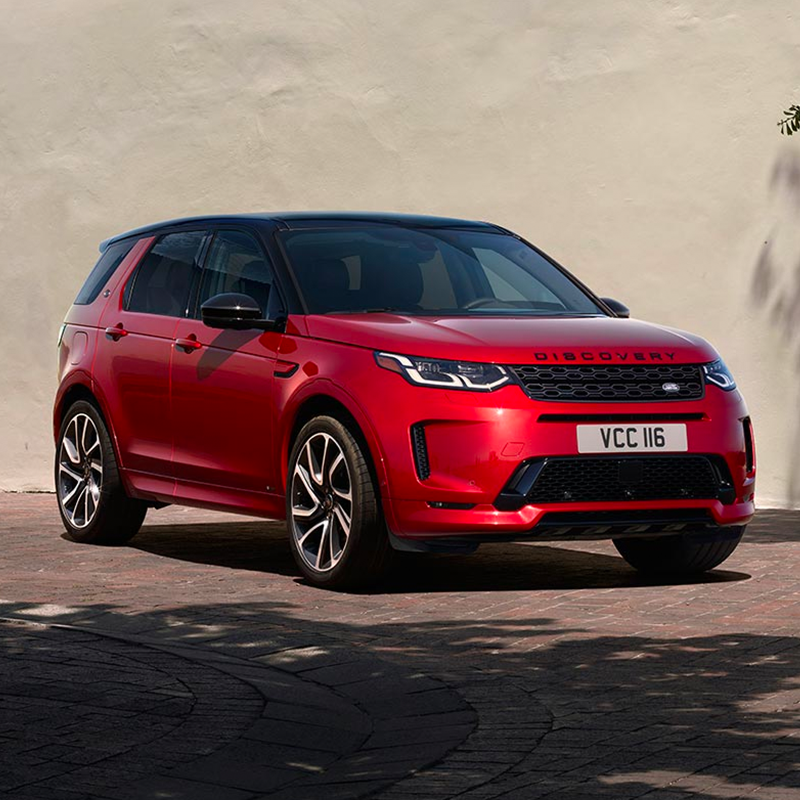 red Land Rover Discovery sport parked in front of a beige color wall and brick flooring