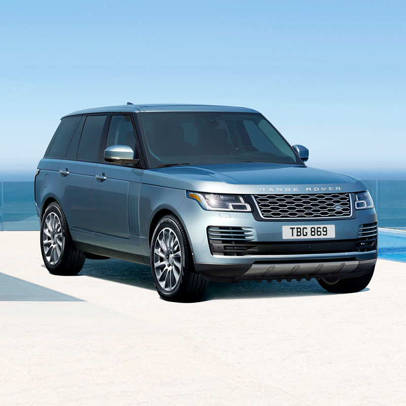 blue Land Rover Range Rover parked on white concrete floor with a the blue ocean in the background
