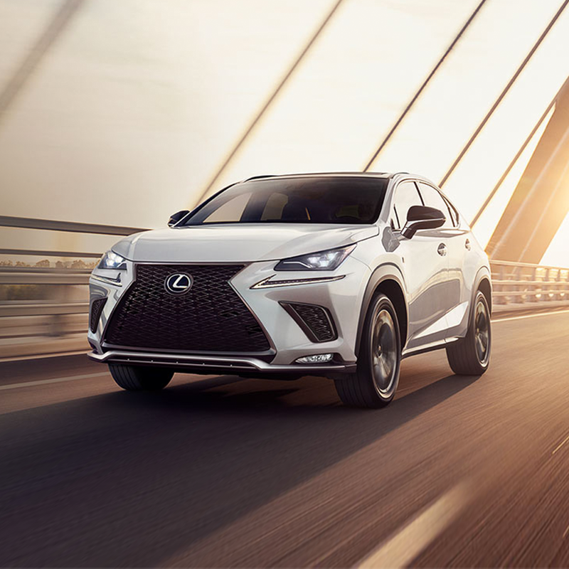 A white Lexus NX suv crossing a bridge during a sunset golden hour