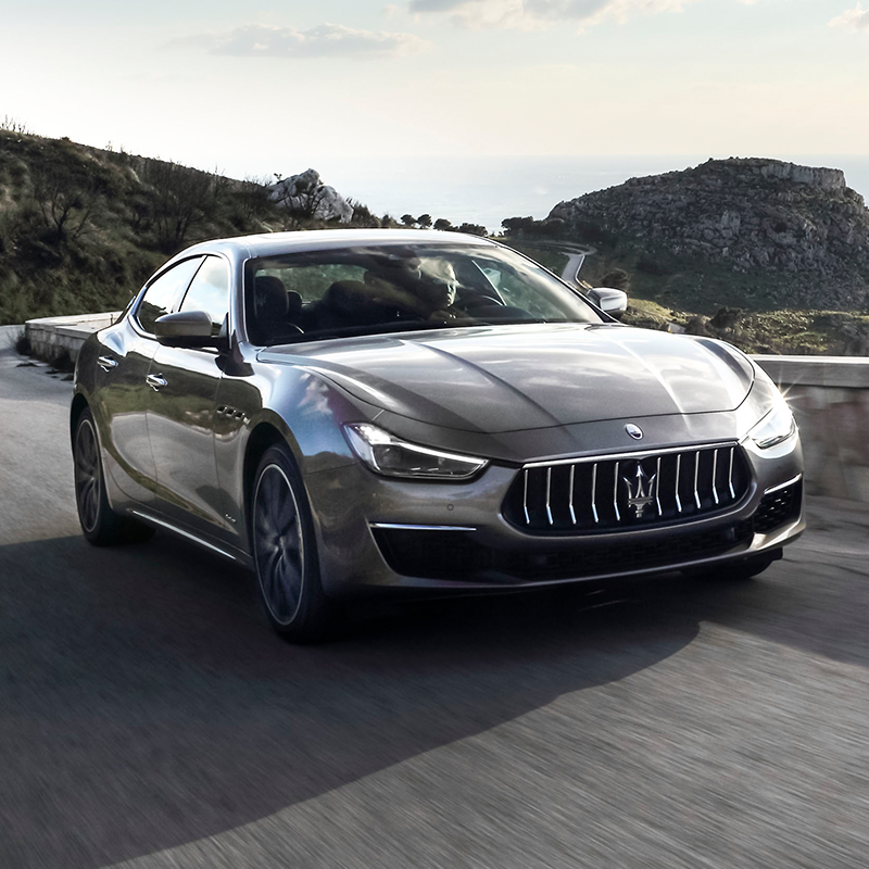 frontal profile of silver maserati ghibli sedan accelerating on a road around a mountain