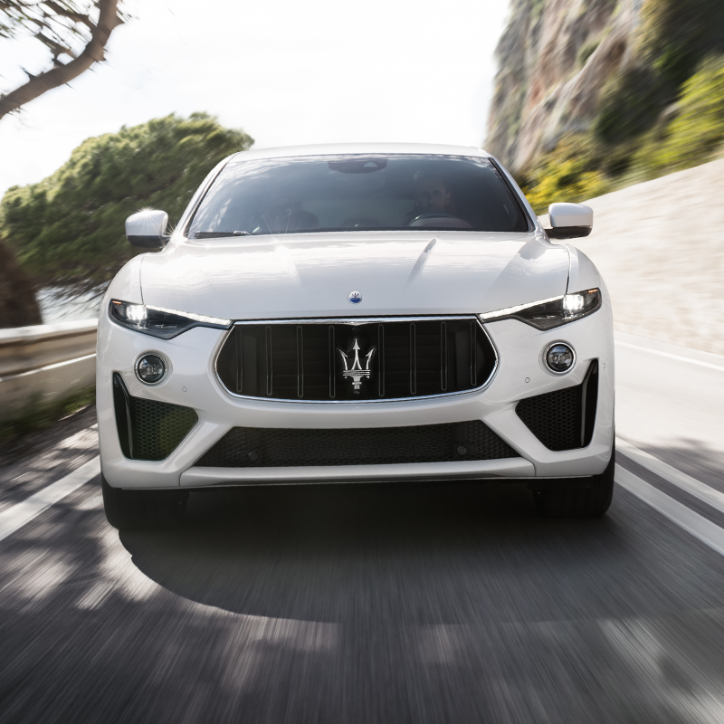 frontal profile of white maserati levante suv accelerating on a road next to a mountain