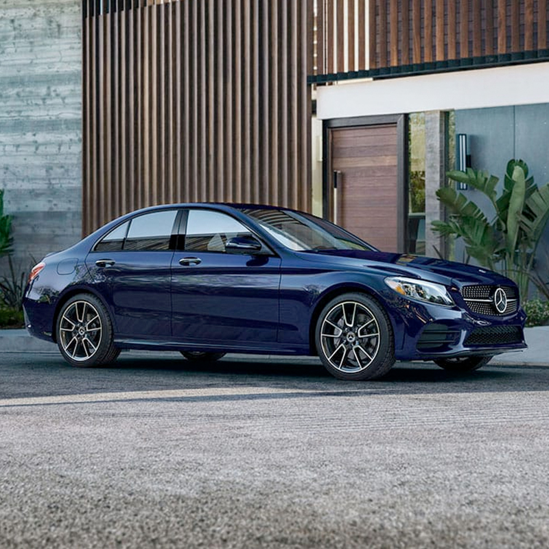 side view of blue Mercedes-Benz C class sedan parked in front of a house