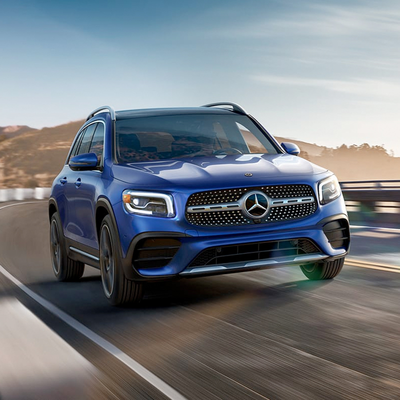 frontal profile of blue mercedes benz glb suv accelerating on a road with mountains in the background