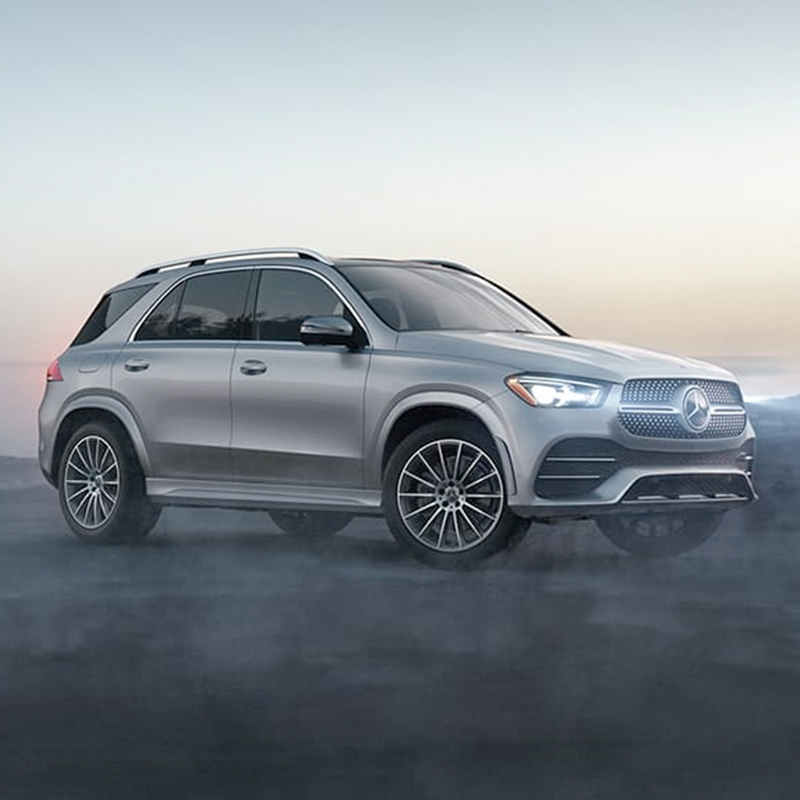 side view of Mercedes-Benz GLE suv with headlights on on a early foggy morning