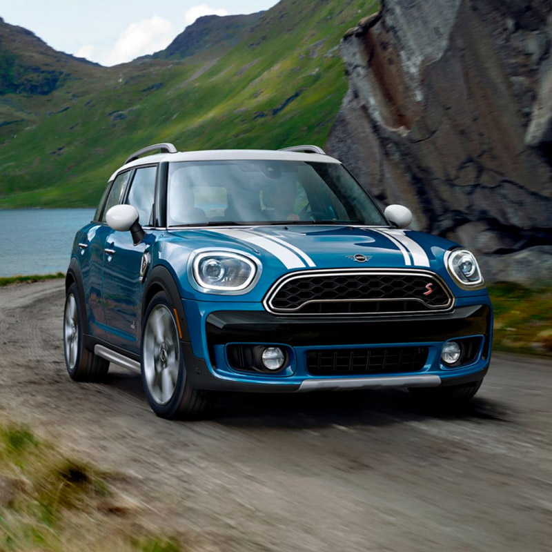 frontal view of mini countryman s on a dirt road with mountains in the background