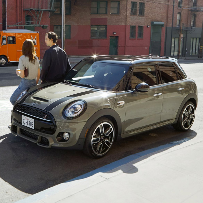 two people leaning on the side of a gray mini 4 door hardtop