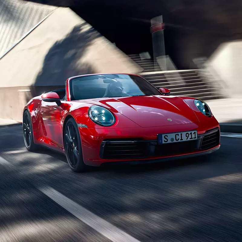 frontal profile of red Porsche 911 Carrera accelerating on the road