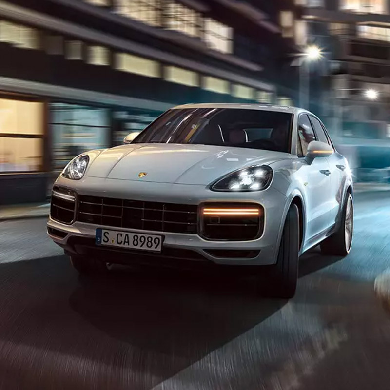 frontal profile view of porsche Cayenne suv accelerating on city streets at night time