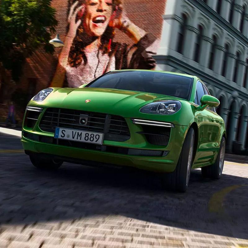 Green Porsche Macan driving downton
