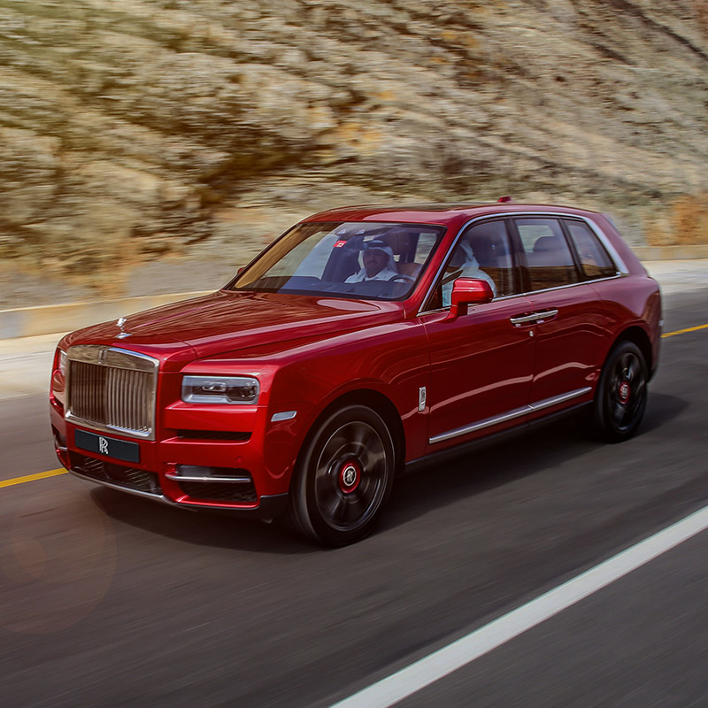 red Rolls-Royce Cullinan suv driving on a road with big rocks in the background