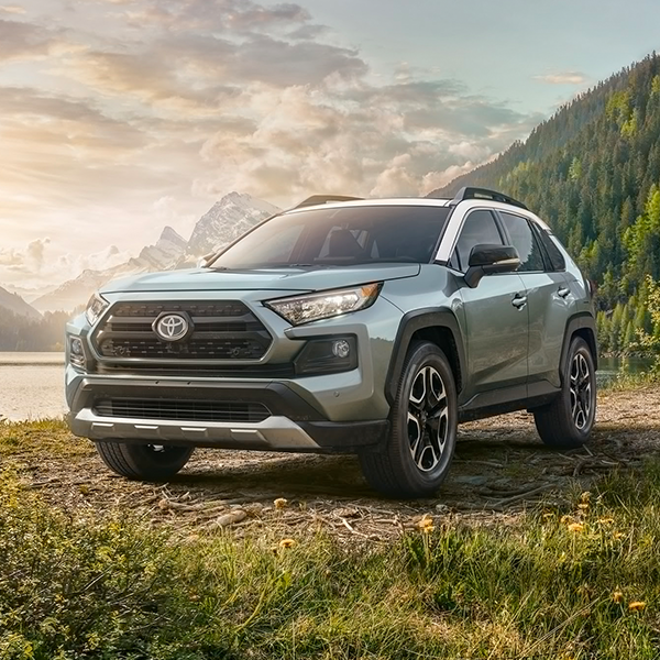 grey toyota Rav4 suv parked in front of a lake with mountains in the background
