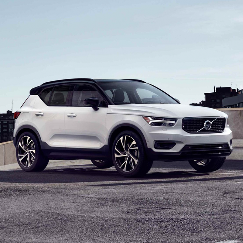 white Volvo XC40 parked at the top level of a multifloor parking space.
