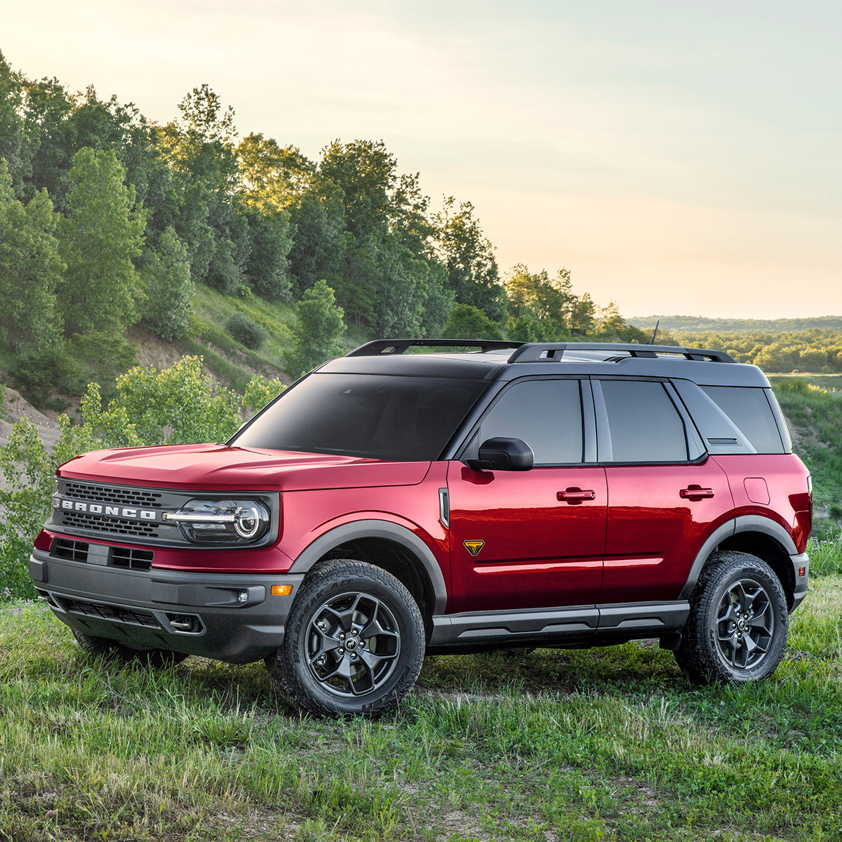 side profile of ford bronco sport in red color parked  on grass surrounded by green mountains