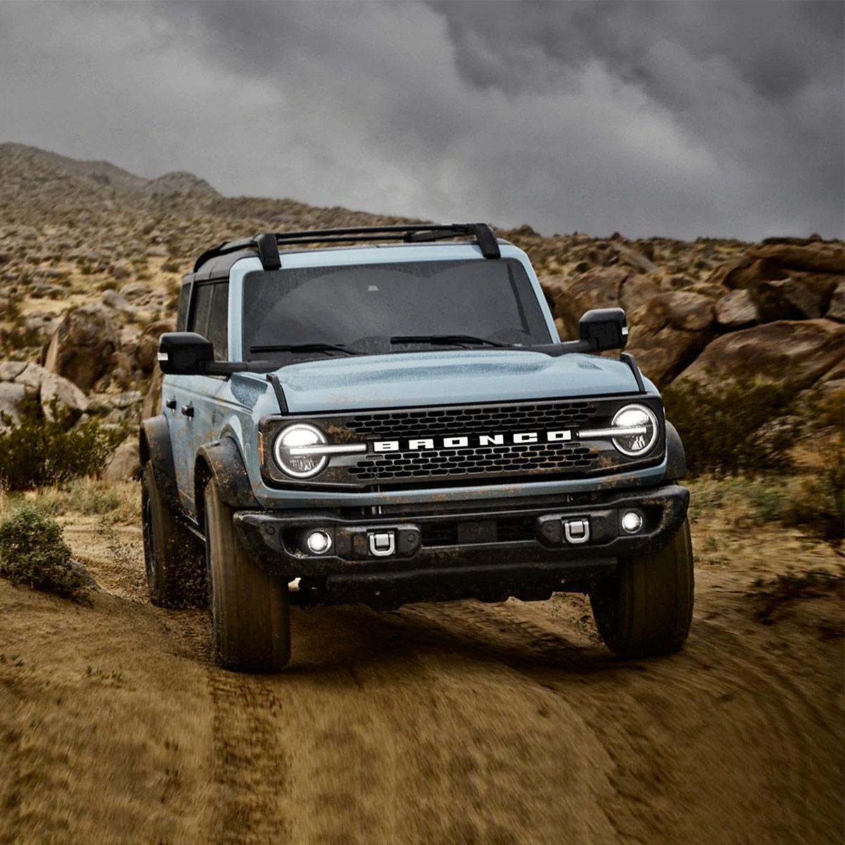 frontal profile of ford bronco in light blue color driving on a dirt terrain with rocky mountains in the background