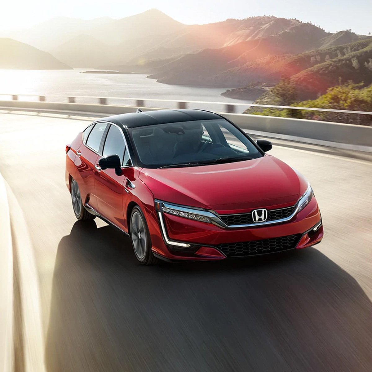 frontal profile of honda clarity sedan in red color driving on a bridge curve at sunset