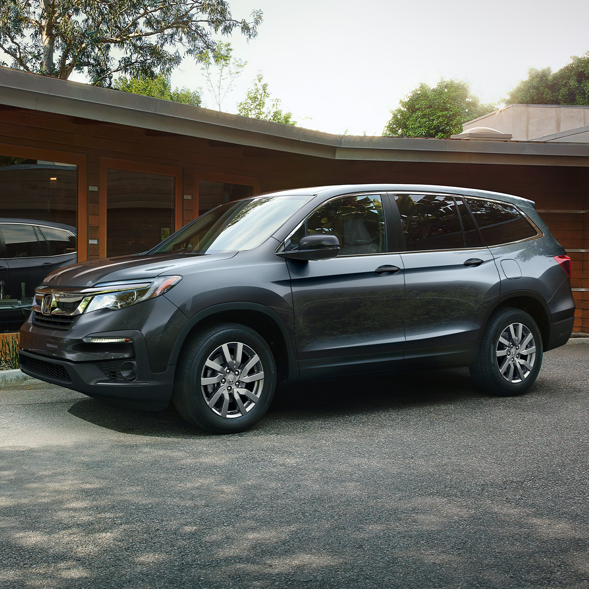 side profile view of dark blue Honda pilot suv parked on a driveway