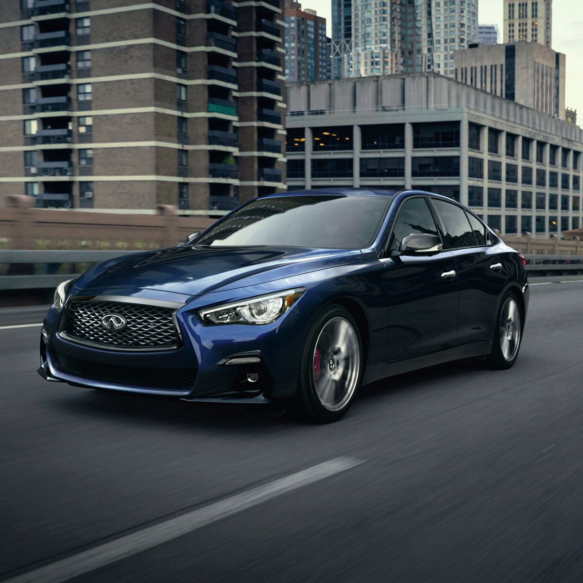 frontal profile of INFINITI Q50 sedan in blue color driving on top of a bridge with buildings in the background