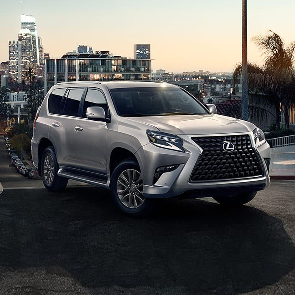 side profile of lexus GX suv in silver color driving on a hill road with city buildings on the horizon