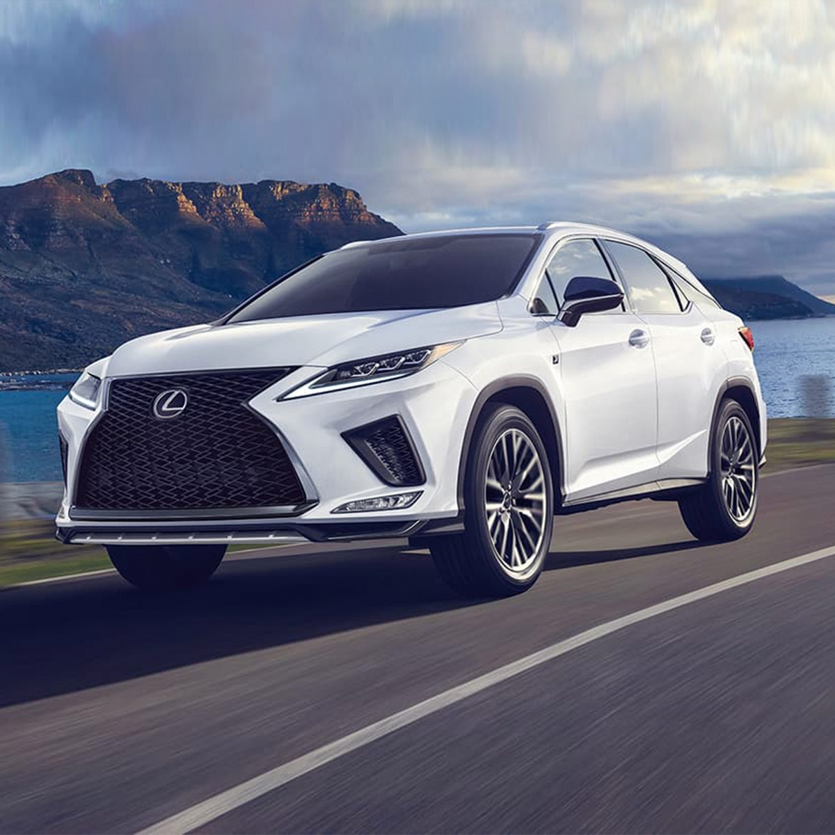 side profile of lexus RX suv in white color driving on a pavement road next to a lake with mountains in the background