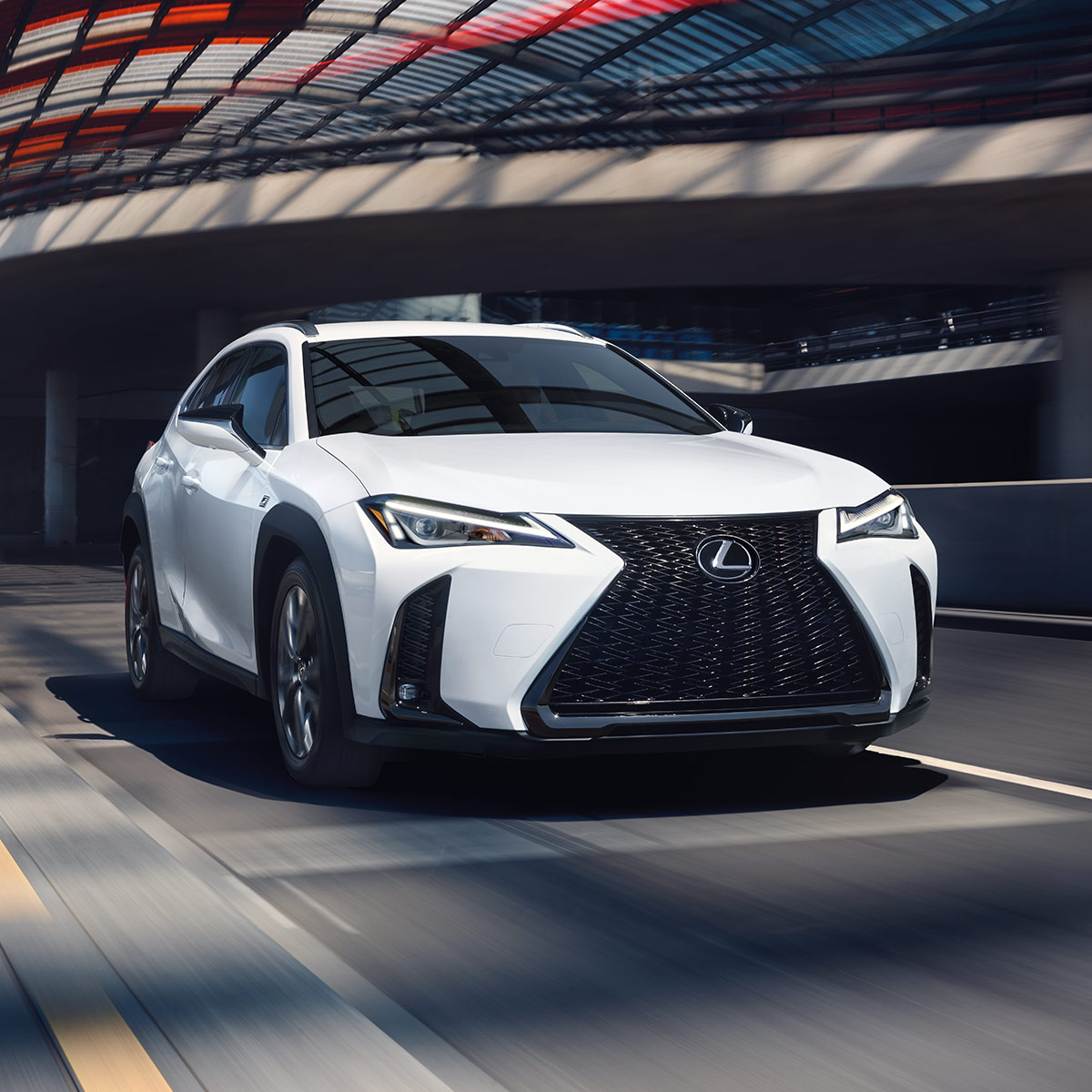 frontal profile of lexus ux suv in white color driving under a tunnel at daytime
