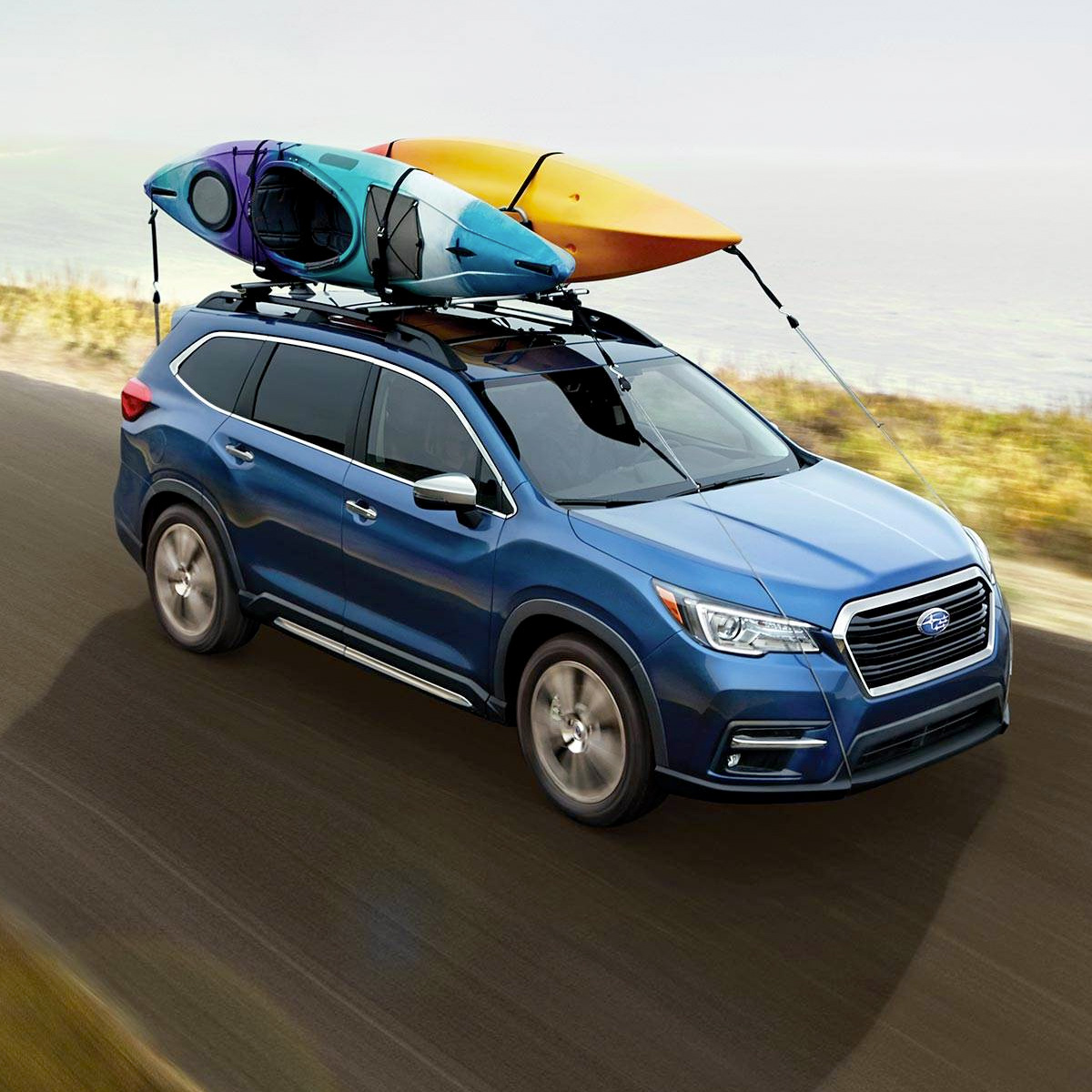 side profile of subaru ascent in blue color carrying kayaks on top of the roof racks driving on a road next to a beach