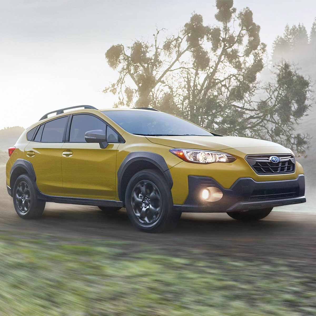 side profile of subaru crosstrek in yellow color with headlights on driving through a foggy morning near a lake