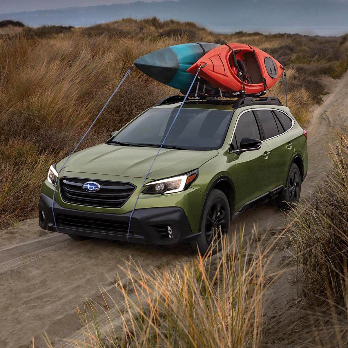 frontal profile of 2021 subaru outback in green color with kayaks on the roof rack driving through sand near a beach
